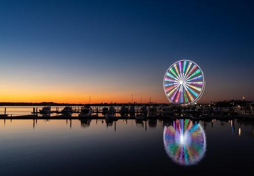Illuminated ferris wheel at National Harbor near the nation capital of Washington DC at sunset