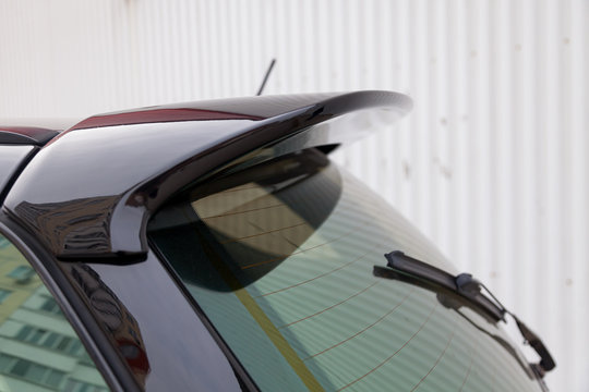 View of the trunk lid of a black car with a plastic spoiler over the rear window to improve the aerodynamics of the vehicle body during tuning for racing.
