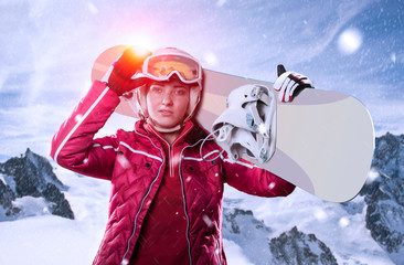 snowboarder with snowboard standing in winter mountain landscape