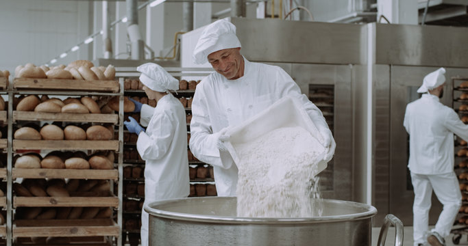 Big bakery industry baker prepare the dough add the flour in a big container background workers arrange the bread and transported the baked bread.