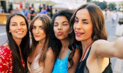 Instagram girls. A selfie photo of multicultural group of four smiley women, posing with various face expressions, which expose joy and contentment.