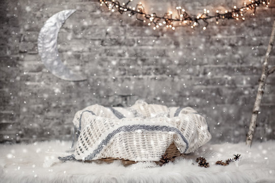 Basket for a newborn baby with a blanket in a Christmas studio interior with a garland, moon and snow