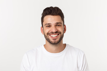 Portrait of a handsome young man smiling against yellow background