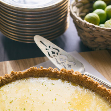 Key lime pie on a cutting board, ready to be served. Shown with whipped cream, extra key limes, plates and pie server.