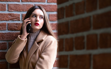 portrait of a girl on the street calling on the phone.a young woman sits against a brick wall and talks on the phone. on young girl autumn beige overcoat. the concept of communication and cellular