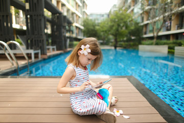 little girl uses tablet sitting close to swimming pool wearing f