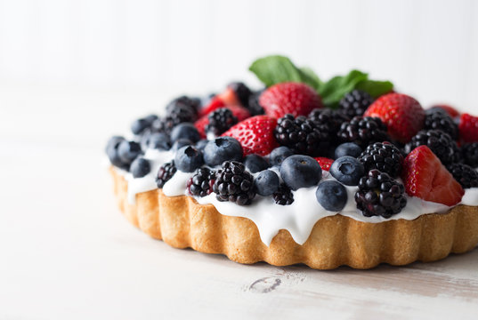 Close up view of a mixed berry tart with blueberries, blackberries and strawberries with mint garnish.