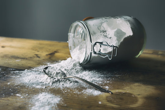 Glass jar filled with arrowroot powder spilled on a wooden table.