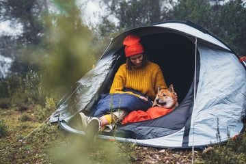 Fototapeten Camping tourist traveler hugging relaxation red shiba inu in camp tent on background foggy forest, smile hiker woman with puppy dog in mist nature trip, friendship love concept, girl resting dog together