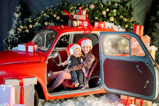 Two sisters in a christmas photo studio. Cute baby girl in a fashionable pin-up dress. many lights and garlands on the Christmas tree. Red retro car. Family celebration. Christmas holiday concept.