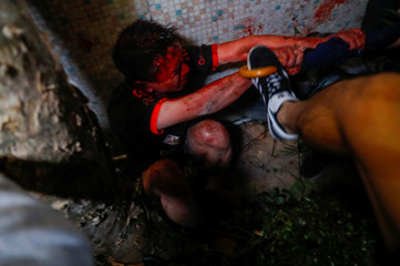 A pro-government supporter scuffles with an anti-government protester, after Chow Tsz-lok, 22, a university student, died after he fell during a protest, at Tseung Kwan O, Hong Kong