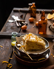 stack of traditional french thin crepes suzette with orange sauce