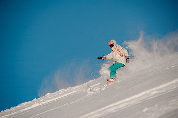 Woman snowboarder riding down the hill in the background of clear sky