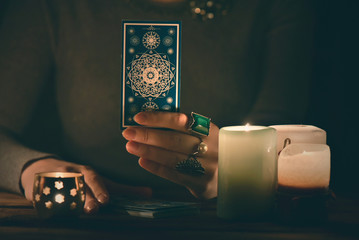 Fortune teller reading a future by tarot cards in the light of candle concept. Wall mural