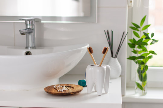 Bio-degradable, compostable bamboo toothbrushes in a tooth shape cup in a bathroom white interior. Green plant decor in background.