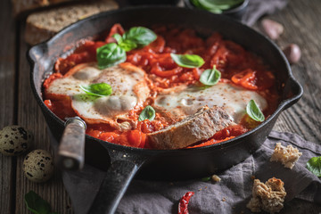 Delicious shakshuka with eggs, tomatoes and herbs