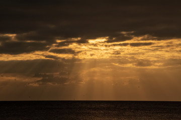 Dark cloudscape opening up with beams of sunlight shining through to Gulf of Mexico during sunset