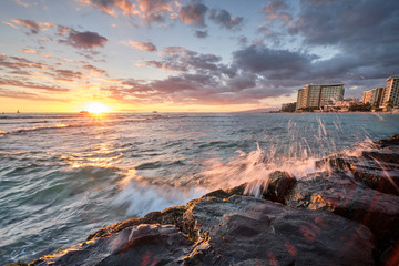 Sunset at Waikiki Beach, Hawaii with waves crashing again rocks