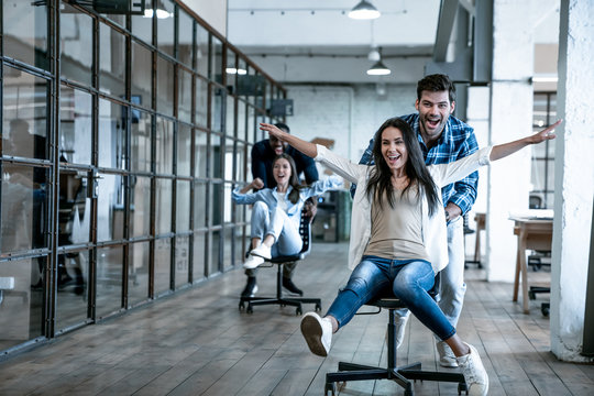 Work hard play hard. Four young cheerful business people in smart casual wear having fun while racing on office chairs and smiling