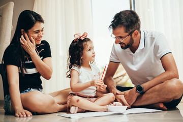 Happy family playing with daughter in the living room