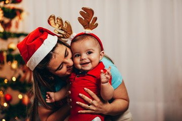 Mother and her baby playing at home on Christmas holiday