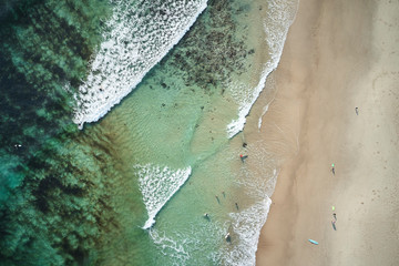 Group of surfers handing out over a reef just of the beach catching waves in Australia
