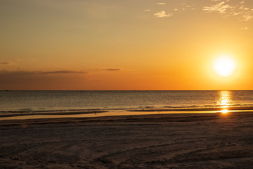 Sunset scene at Fort Myers Beach, FL, with bright orange color, sandpiper silhouette and reflection, and seagulls