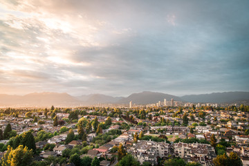 View of East Vancouver and Brentwood, Burnaby skylines with mountains backdrop during and epic summer sunset Fotomurales