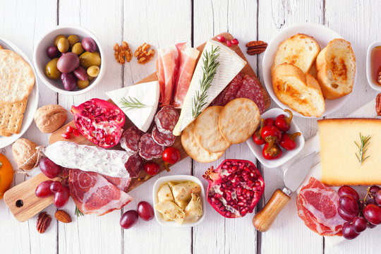 Charcuterie board of assorted cheeses, meats and appetizers. Above view table scene on a white wood background.