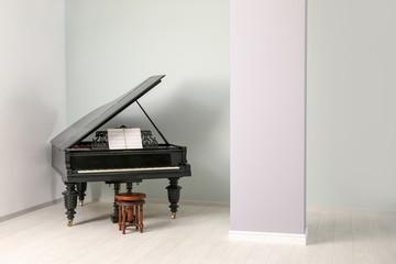 Stylish grand piano in light room
