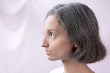 Portrait of a brown-eyed girl in profile on a pink background