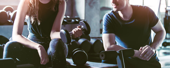 Crop image of beautiful sport girl with dumbbell in hand with personal trainer in professional gym,...