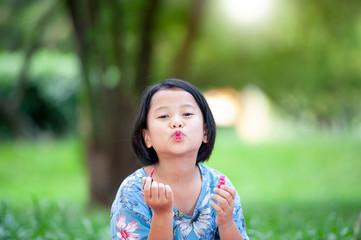 Funny cute asian yellow skinned baby girl rouge her lips with a mother's lipstick outdoor in the park. playing Growing up, leadership, copying female psychology behavior concept.