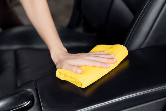 Car wash service, girl worker cleaning interior modern microfiber and console auto