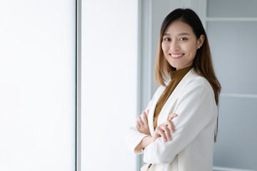 Attractive young Asian smiling woman in smart casual in office