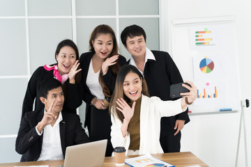 Asian business team taking selfie by smartphone,business people concept.