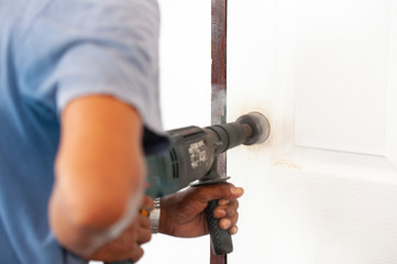 Intervention to secure a door of a home, Installation of the door lock, Wood processing, auger drilling, close up with copy space
