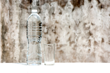 A plastic water bottle and water glass  on the table with old brick wall background.