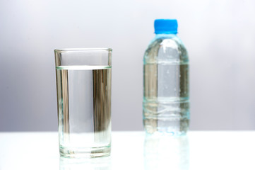 A glass of fresh drinking water. Close up purified fresh drink water on table and a fresh drinking water bottle on white background.