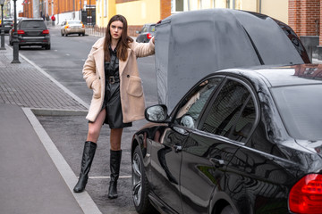 Woman waiting support near her broken car. a young woman stands near her broken car and does not know what to do with it.The car opened the hood. On young girl autumn overcoat. The car is black