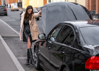 a young woman stands near her broken car and does not know what to do with it.The car opened the hood. On young girl autumn overcoat. The car is black.Weather autumn day.