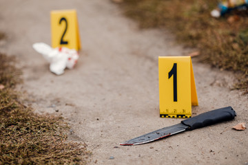 Crime scene investigation, bloody knife with crime markers on the ground, evidence of murder - fototapety na wymiar