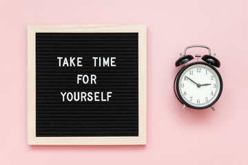 Take time for yourself. Motivational quote on letterboard and black alarm clock on pink background. Top view Flat lay Copy space Concept inspirational quote of the day
