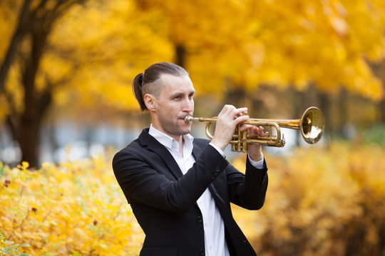 young European handsome trumpeter in formal clothes playing his musical instrument golden trumpet among trees with yellow leaves in autumn park