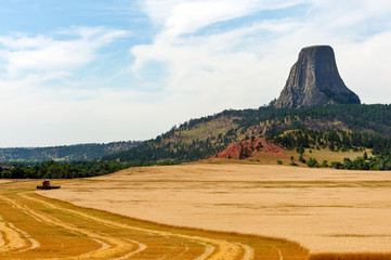 Combine harvesting crops near Devils Tower National Monument (Bear Lodge in Native american culture), part of the Black Hills in Wyoming