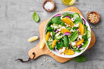 Fresh spinach salad with oranges, feta (ricotta) cheese, red onion and pine nuts .