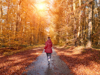 Woman running and training in fall nature