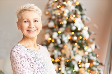 Holiday spirit, celebration and festivity concept. Picture of beautiful middle aged Caucasian woman wearing stylish dress and short haircut wishing you Happy Christmas and New Year, posing at tree