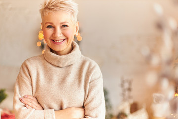 Close up image of fashionable overjoyed European middle aged woman in turtleneck cashmere sweater keeping arms crossed and smiling confidently, waiting family for festive dinner at Christmas Eve