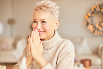 Indoor shot of overjoyed cheerful mature short haired woman in stylish sweater holding hands pressed together at her mouth, smiling broadly, receiving New Year's gift, can't hide her excitement